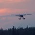 Float plane coming in for landing at sunset